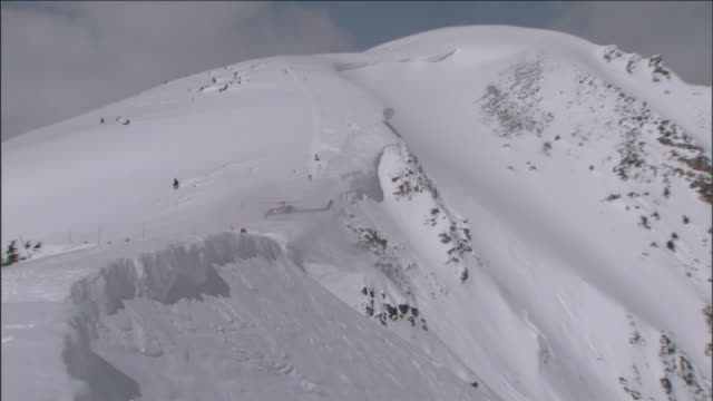 a rescue helicopter flies over snow-covered mountains. - hill stock videos & royalty-free footage