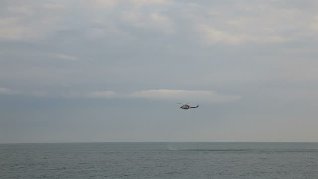 Rescue helicopter hovering over sea ( Timelapse)