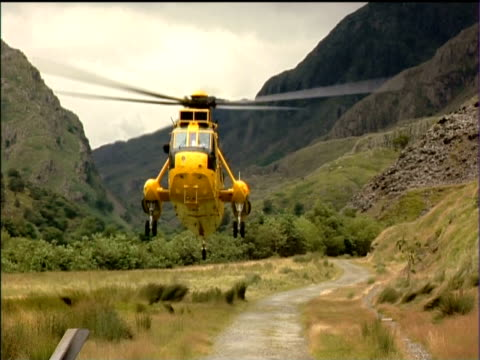rescue helicopter lands on valley floor snowdonia national park - snowdonia stock videos & royalty-free footage