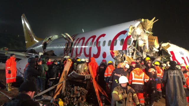 vídeos de stock e filmes b-roll de rescue members and firefighters work after pegasus airlines plane skidded off the runway at istanbul's sabiha gokcen airport on february 05, 2020 in... - acidente de avião