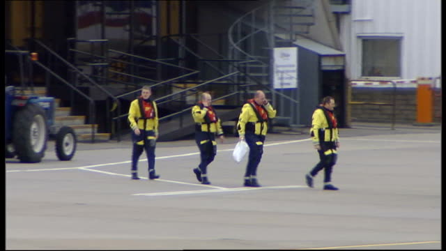 rescue operation launched after major security alert on north sea oil rig search and rescue crew along to helicopter at heliport - helicopter landing pads stock videos and b-roll footage