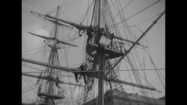 rescue personnel at ship yardarm with person in breeches buoy; people at dock look up through netting to men on mast / vs weakened man helped from... - 弱い点の映像素材/bロール