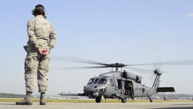 33 rescue squadron hh60 pave hawk aircrew and pararescuemen from 31 rescue squadron prepare for a training mission on the flightline during exercise... - 米軍点の映像素材/bロール