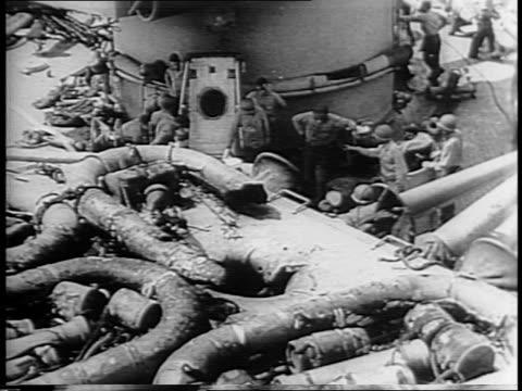 Rescue squads in gas masks clear casualties after a Nazi bomb hit a gun turret on USS Savannah climb out of door in turret and remove masks /...
