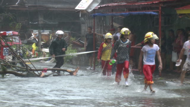 rescue team walks through storm surge flooding after typhoon haiyan - rescue stock videos & royalty-free footage