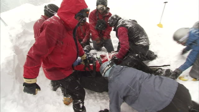 a rescue team works together to get an avalanche victim to safety. - rescue stock videos & royalty-free footage