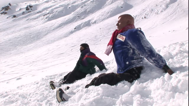 rescue training mannequins sit on a snow-covered slope. - rettungssanitäter stock-videos und b-roll-filmmaterial