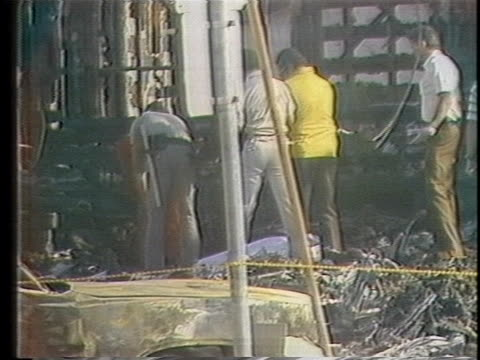 rescue worker covers a body in the aftermath of a san diego air crash as others stand amidst the wreckage of the debris. - 1978 stock videos & royalty-free footage
