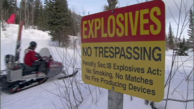 "a rescue worker rides a snowmobile pulling a sled past a sign reading, ""explosives no trespassing"". - rescue worker stock videos & royalty-free footage"