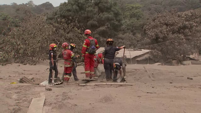 rescue workers attempt to access a home buried under volcanic ash following the devastating eruption of the fuego volcano outside of guatemala city... - pyroklastischer strom stock-videos und b-roll-filmmaterial