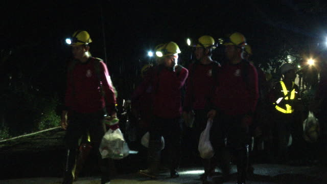 rescue workers depart the tham luang cave area after divers evacuated four of the boys among a group of 13 trapped in a flooded cave in khun nam nang... - rescue stock videos & royalty-free footage