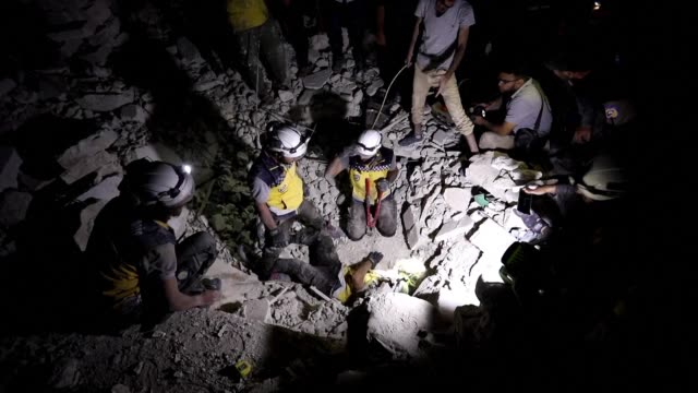 stockvideo's en b-roll-footage met rescue workers known as white helmets search for survivors following syrian government forces air strikes in the rebel town of orum al-kubra in the... - clean