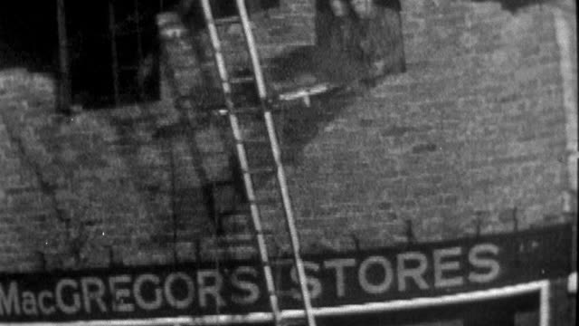 1957 montage rescue workers lower a survivor on stretcher from the roof of macgregor's stores following an atomic attack / united kingdom - 1957 stock videos & royalty-free footage