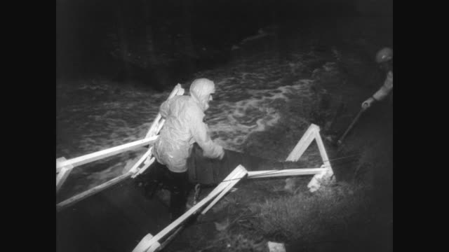 rescue workers on a bridge in the rain during the south central california flooding crisis / rescuers are roped together and flood water is rushing... - 1966 stock-videos und b-roll-filmmaterial