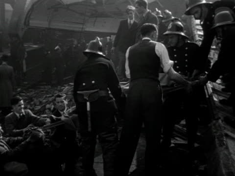 rescue workers remove a dead body from the wreckage of the 1952 harrow and wealdstone train crash. - harrow stock videos & royalty-free footage
