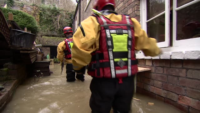 rescue workers wading through flooded streets in shropshire - walking in water stock videos & royalty-free footage