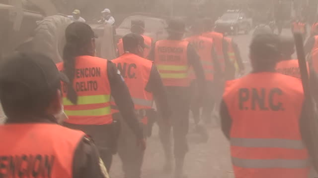 rescue workers walk down a roadway covered in ash following the devastating eruption of the fuego volcano outside of guatemala city in guatemala - pyroklastischer strom stock-videos und b-roll-filmmaterial