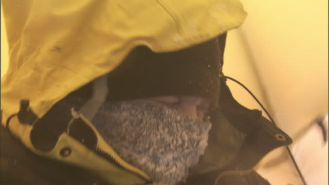 Rescue workers wearing goggles warm up in a tent during a blizzard.