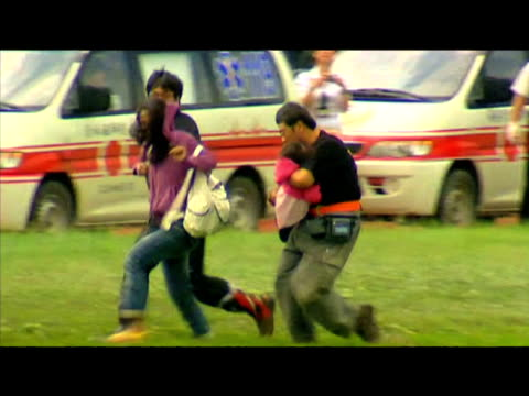 rescued victims of typhoon morakot run across grass to safety taiwan 12 august 2009 - taiwan stock videos & royalty-free footage
