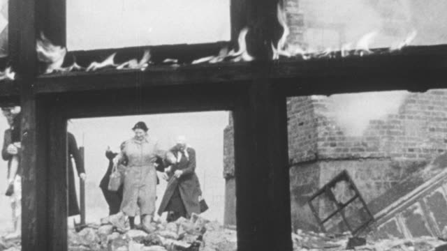 vidéos et rushes de 1956 montage rescuer carrying injured survivor from burning building, child stuck underneath rubble, and rescuer directing survivors through rubble after a world war ii air raid / united kingdom - 1956