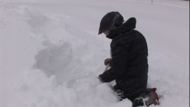 a rescuer digs a hole in the side of a snow hill. - survival stock videos & royalty-free footage