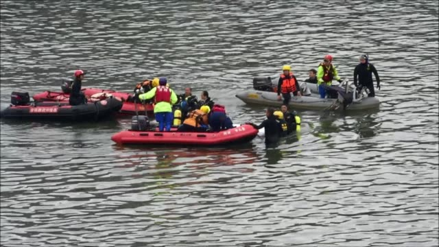 Rescuers and divers search for missing passengers at the crash site of the Transasia plane in the Keelung river in New Taipei City