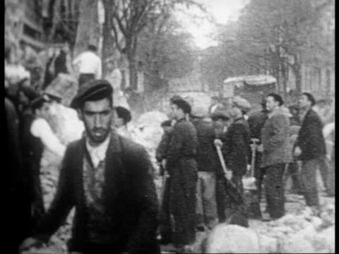 vidéos et rushes de rescuers dig through the rubble of building destroyed by fascist bomb searching for surivivors / a victim of the bombing is pulled from rubble - bombardement