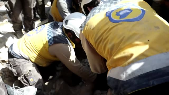 vídeos y material grabado en eventos de stock de rescuers of the syrian civil defence the white helmets look for survivors in the rubble after regime airstrikes that targetted the town of ariha in... - trabajador de rescate