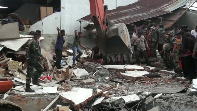 Rescuers scrabbled through the rubble of shattered homes shops and mosques in search of survivors Wednesday after a powerful earthquake struck...