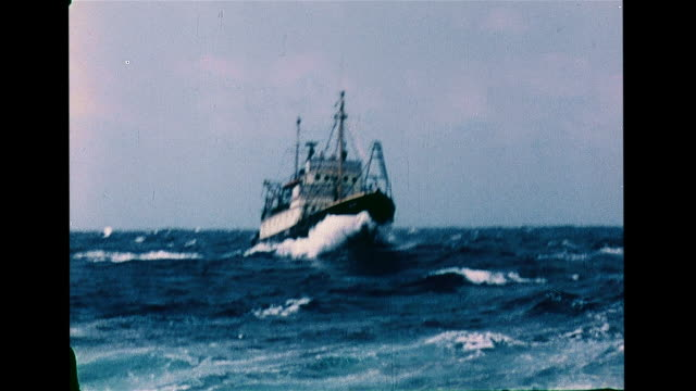 research boat on rough sea, rising swells. aerial: icebreaker ship moving into & over frozen water ice sheet. xws ship off coast w/ mountains bg. vs... - 測定器点の映像素材/bロール