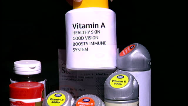 research suggests vitamin supplements may increase risk of death; bottles of vitamins and supplements as bottles picked up of vitamin a, vitamin e... - beta carotene stock videos & royalty-free footage