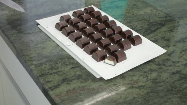 research technician slices freshly made chocolates on a board during the testing process in the flavor research laboratory at givaudan sa... - scented stock videos & royalty-free footage