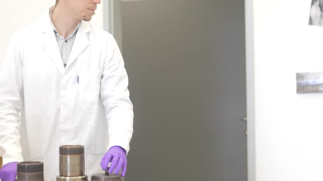 Researcher and His Assistant Preparing Lead Container For Scientific Sample Examination