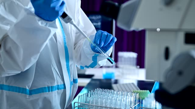 researcher doing virus research. wearing a protective suit. - biochemistry stock videos & royalty-free footage