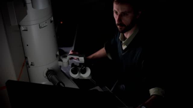 vídeos de stock, filmes e b-roll de pesquisador examinar exemplos usando computador e microscópio digital - microscópio