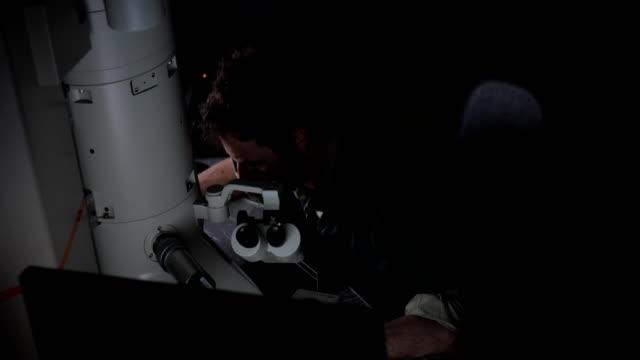 researcher examining samples using computer and digital microscope - microscopio elettronico a scansione video stock e b–roll