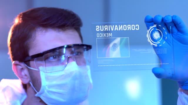 vídeos de stock e filmes b-roll de researcher looking at coronavirus results. mexican flag on digital screen in laboratory - méxico