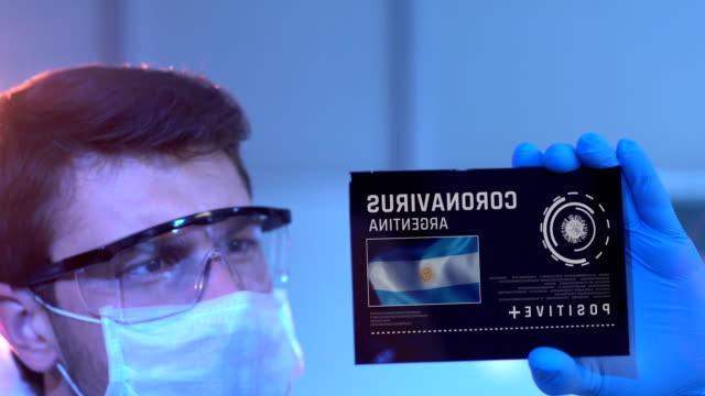 forscher blick auf coronavirus ergebnisse von argentinien. argentinische flagge auf digitaler leinwand im labor - argentinische flagge stock-videos und b-roll-filmmaterial