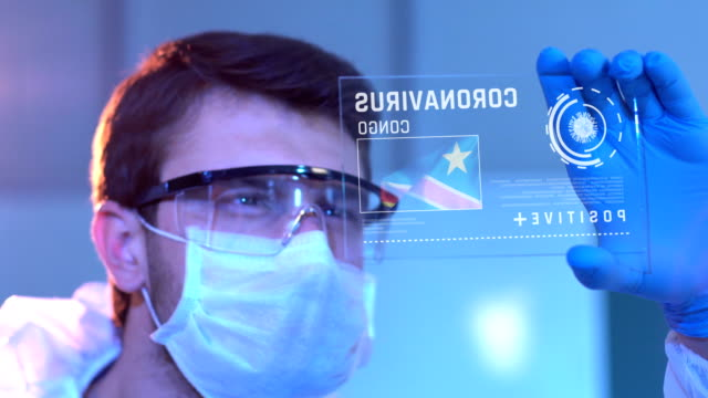 researcher looking at coronavirus results of congo. congolese flag on digital screen in laboratory - democratic republic of the congo stock videos & royalty-free footage