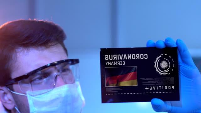 forscher mit blick auf coronavirus-ergebnisse deutschlands auf digitalem bildschirm im labor - diagramm stock-videos und b-roll-filmmaterial