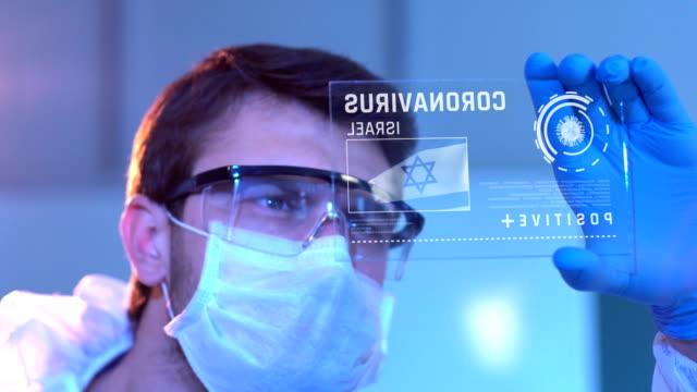 researcher looking at coronavirus results of israel. israeli flag on digital screen in laboratory - israel stock videos & royalty-free footage