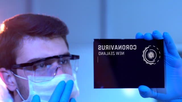 researcher looking at coronavirus results of new zealand. new zealand flag on digital screen in laboratory - medical occupation stock videos & royalty-free footage