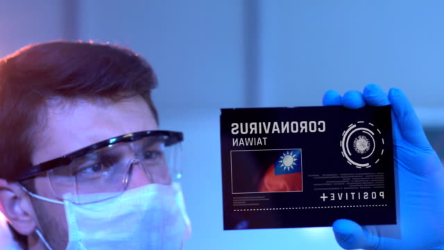 researcher looking at coronavirus results of taiwan. taiwanese flag on digital screen in laboratory - taiwanese flag stock videos & royalty-free footage