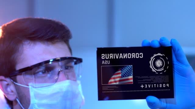 アメリカ合衆国のコロナウイルスの結果を見る研究者。実験室でデジタル画面に米国旗 - プラス記号点の映像素材/bロール