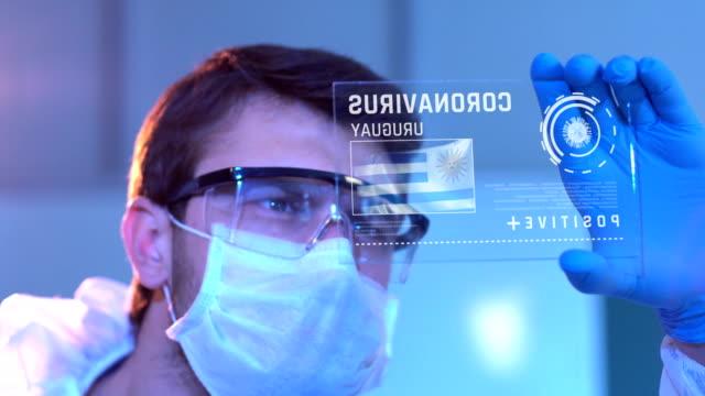 researcher looking at coronavirus results of uruguay. uruguaian flag on digital screen in laboratory - uruguaian flag stock videos & royalty-free footage