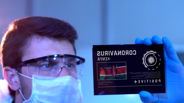 researcher looking at coronavirus results with kenyan flag on digital screen in laboratory - kenyan flag stock videos & royalty-free footage