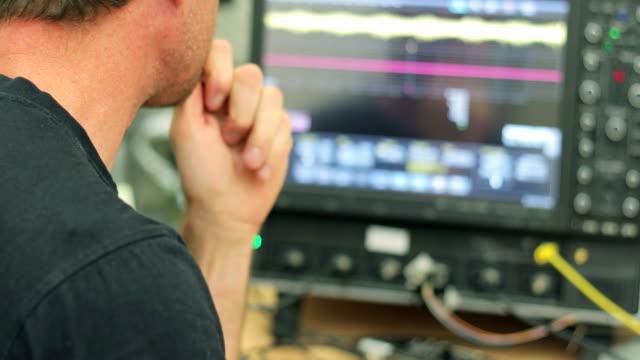 有機半導体における過渡光電流測定をオシロ スコープで見ている研究員 - レーザー点の映像素材/bロール