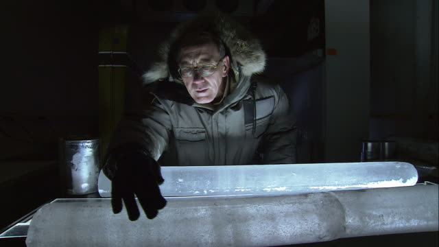 TS Researcher touching and examining ice sample in darkened laboratory / Ohio, United States