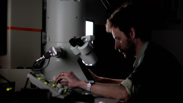 forskare använder fältet utsläpp elektronmikroskop att granska vetenskapliga prov - biokemi bildbanksvideor och videomaterial från bakom kulisserna