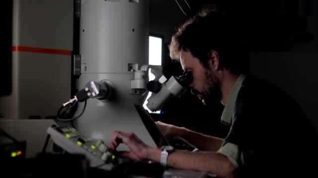 vídeos de stock, filmes e b-roll de pesquisador usando microscópio eletrônico de emissão de campo para examinar a amostra científica - microscópio